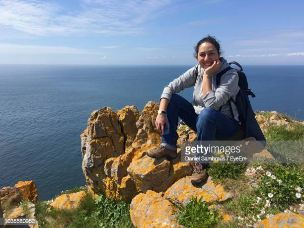 Portrait Of Female Hiker Smiling While Sitting On Cliff Against Sea