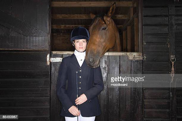 portrait of female horseback rider with horse in stable - riding hat stock pictures, royalty-free photos & images