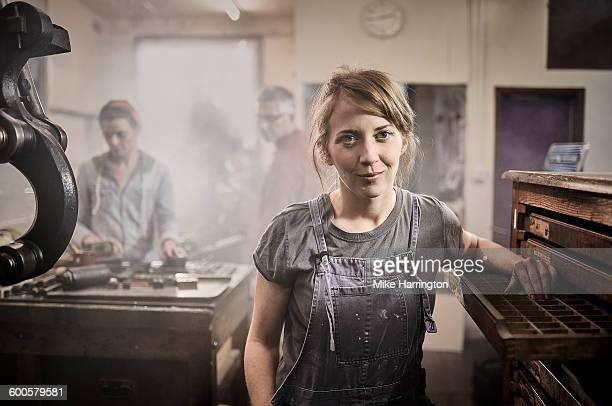Portrait of female in letterpress printing studio.