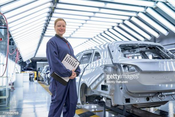 Portrait of female inspector in paint shop in car factory
