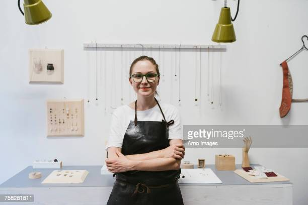 Portrait of female jeweller with arms folded in jewellery workshop