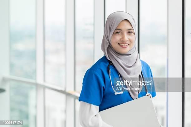 retrato de mulher médica da malásia carregando registros médicos - hijab - fotografias e filmes do acervo