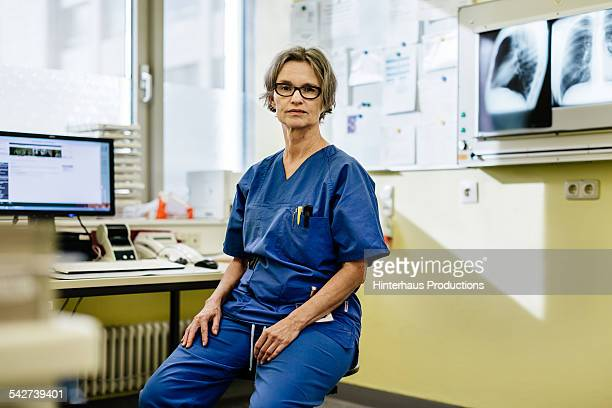 portrait of female mature doctor sitting - leanincollection stock pictures, royalty-free photos & images