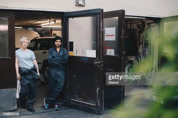 portrait of female mechanics standing at doorway of auto repair shop - auto repair shop exterior stock pictures, royalty-free photos & images