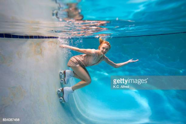 portrait of  female model roller skating underwater in swimming pool in san diego, california. - roller skating stock photos and pictures