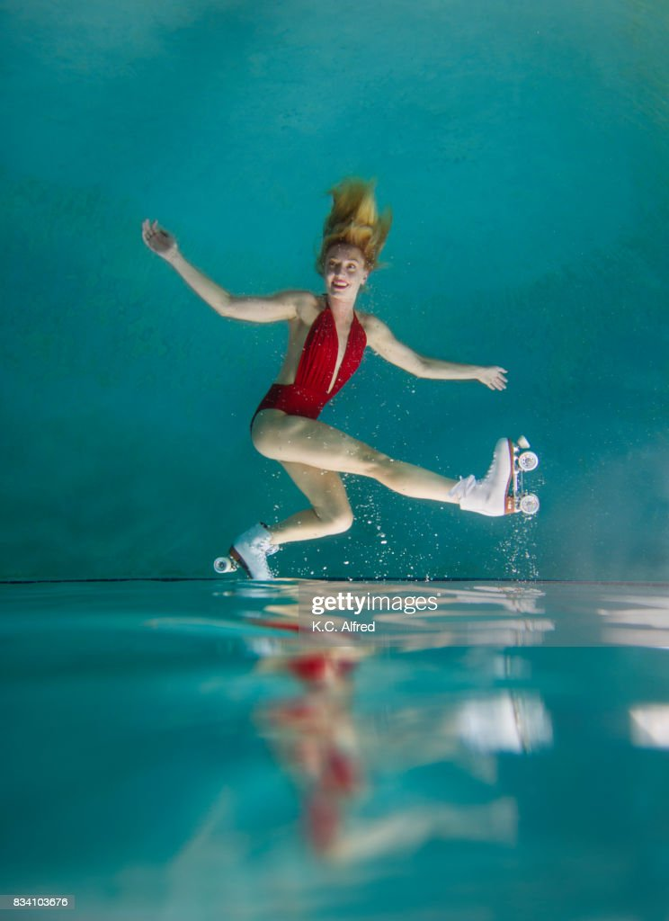 Portrait of  female model roller skating underwater in swimming pool in San Diego, California. : Stock Photo