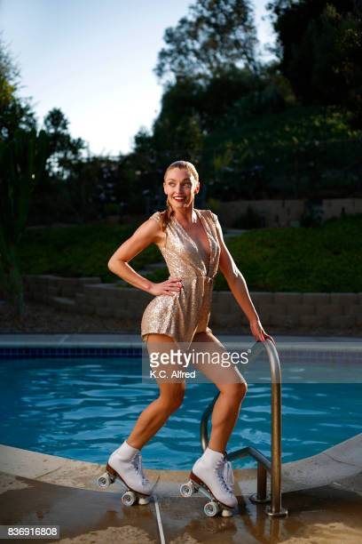 Portrait of  female model wearing a gold jump suit roller skating near a pool in San Diego, California.