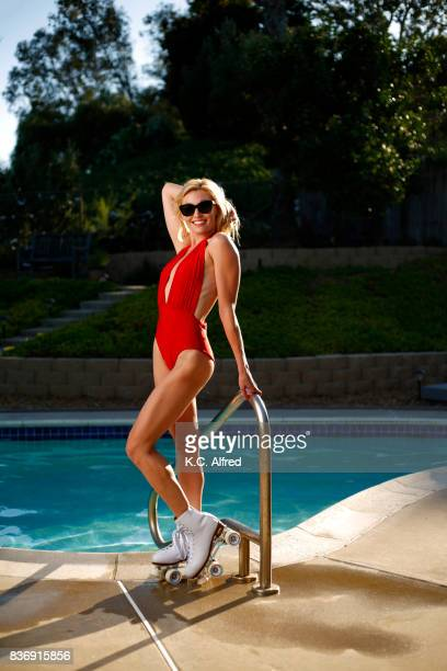 Portrait of  female model wearing a red swimsuit roller skating near a pool in San Diego, California.