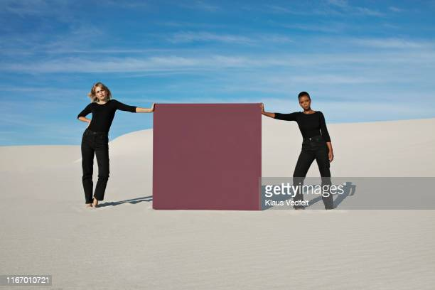 portrait of female models standing by brown portal on white sand at desert - black trousers stock pictures, royalty-free photos & images