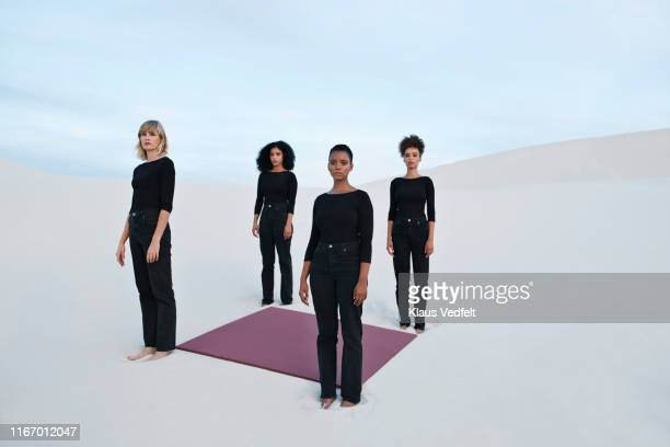 portrait of female models with placard standing at white desert during sunset - black pants stock pictures, royalty-free photos & images