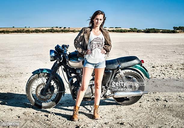 Portrait of female motorcyclist on arid plain, Cagliari, Sardinia, Italy