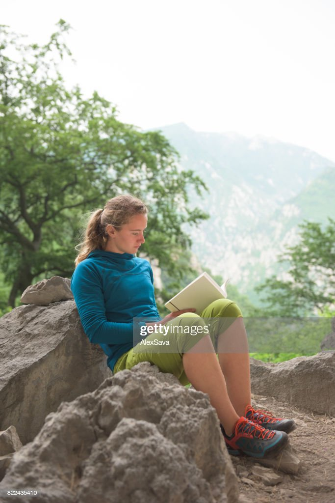 Portrait of female mountaineer reading a book in nature : Stock Photo