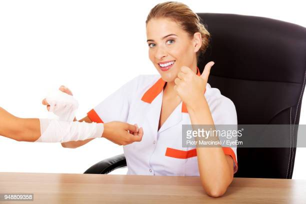 portrait of female nurse examining patient while sitting at table against white background - nurse and portrait and white background and smiling and female and looking at camera stock pictures, royalty-free photos & images