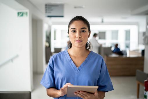 Portrait of female nurse using tablet at hospital 1197650057