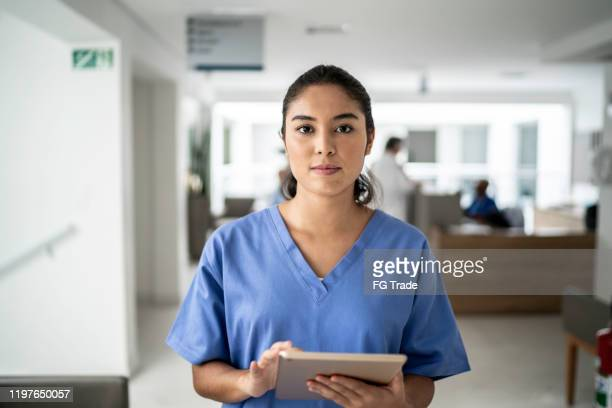 portrait of female nurse using tablet at hospital - serious stock pictures, royalty-free photos & images