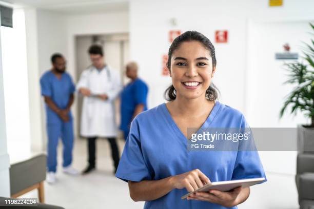 portrait of female nurse using tablet at hospital - medical scrubs stock pictures, royalty-free photos & images