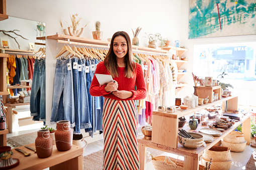 Portrait Of Female Owner Of Independent Clothing And Gift Store With Digital Tablet 1134458349