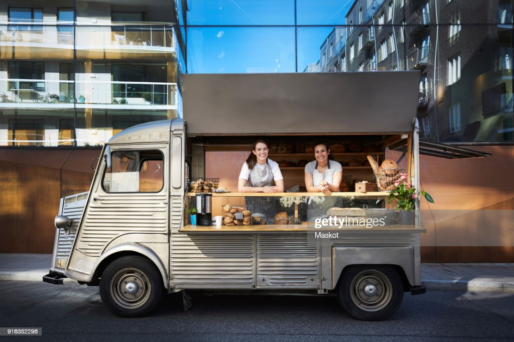 Portrait of female owners in food truck parked on city street against building : Foto de stock