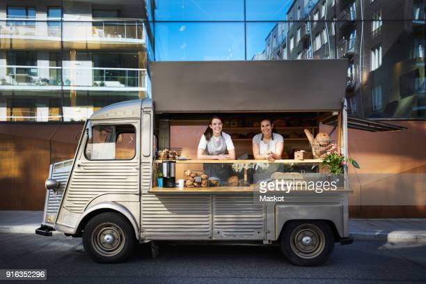 Portrait of female owners in food truck parked on city street against building