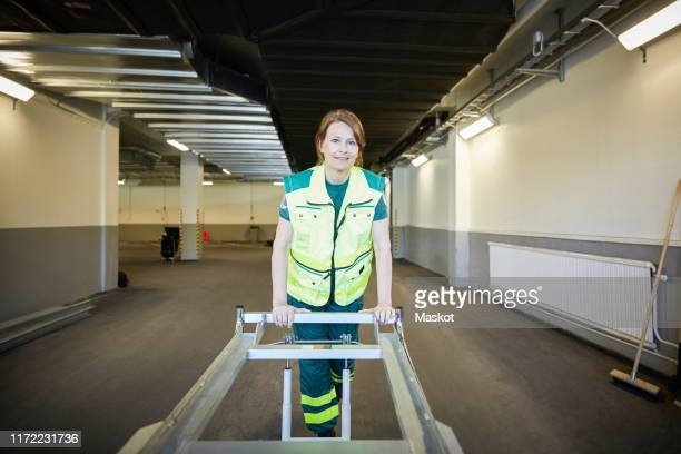 portrait of female paramedic with stretcher in corridor at hospital - rescue worker stock pictures, royalty-free photos & images