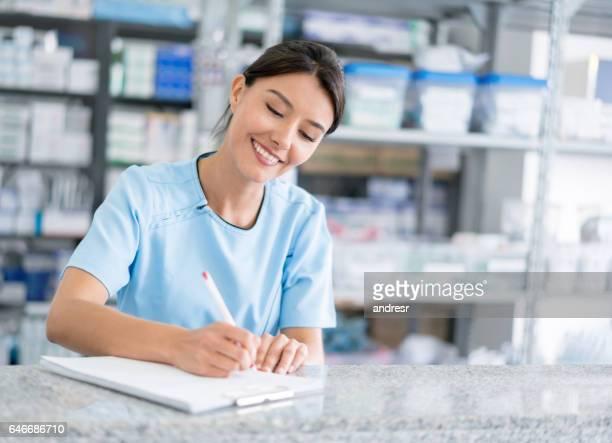 Portrait de femme pharmacien contrôle une liste des médicaments prescrits
