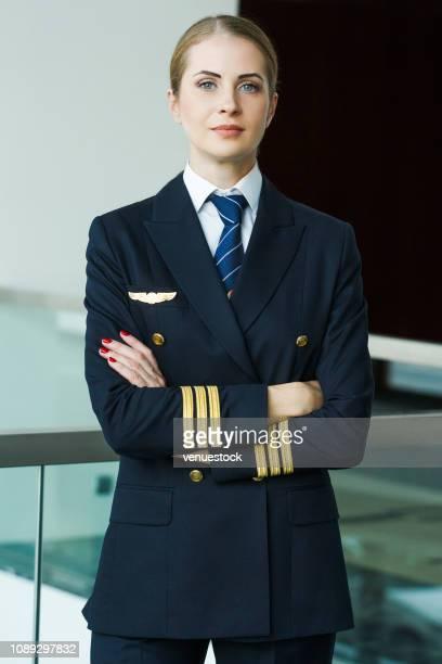 portret van vrouwelijke piloot staande in de luchthaven lobby - vlieger stockfoto's en -beelden