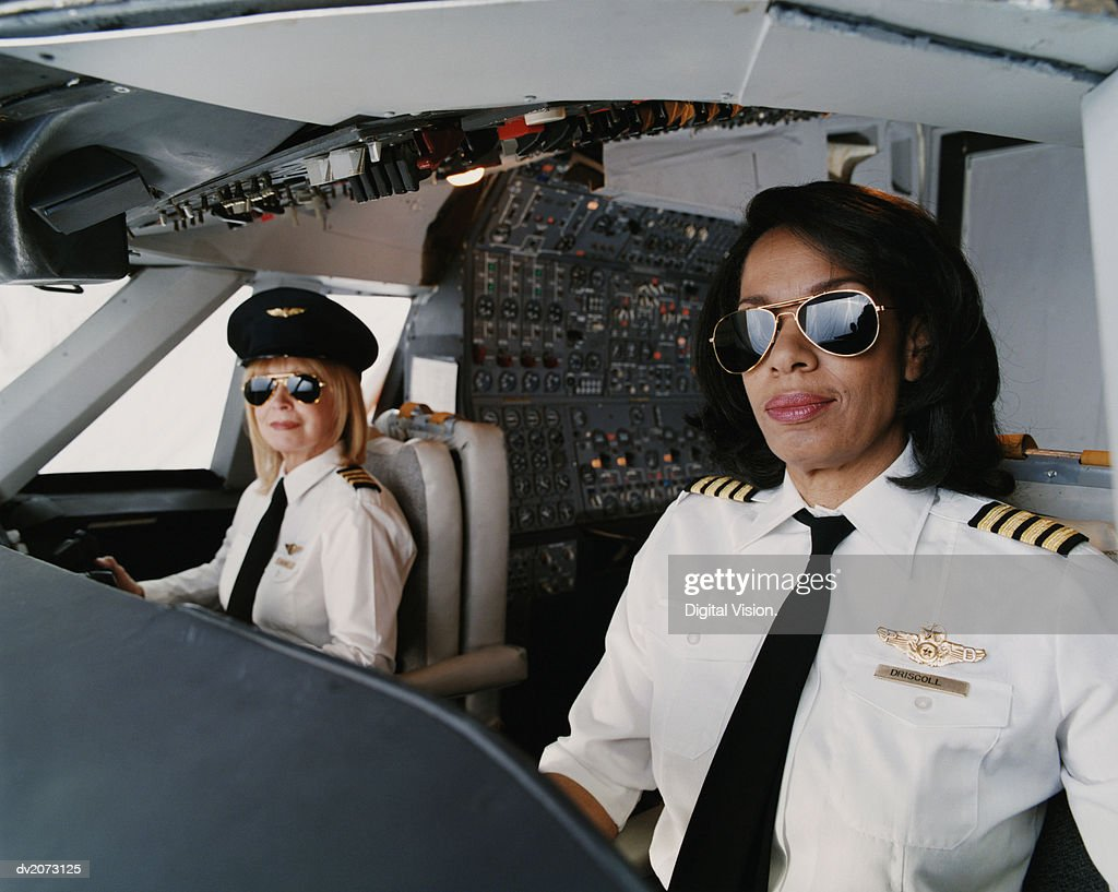 Portrait of Female Pilots Sitting at the Cockpit : Stock Photo
