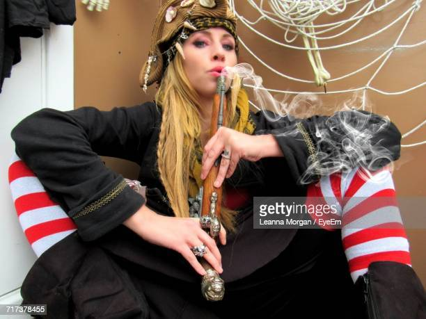 portrait of female pirate blowing smoke emitting from gun - female pirate stock photos and pictures