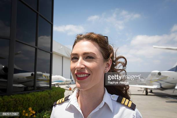 Portrait of female private jet pilot at airport