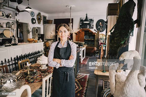 Portrait of female retailer with arms crossed standing in antique shop