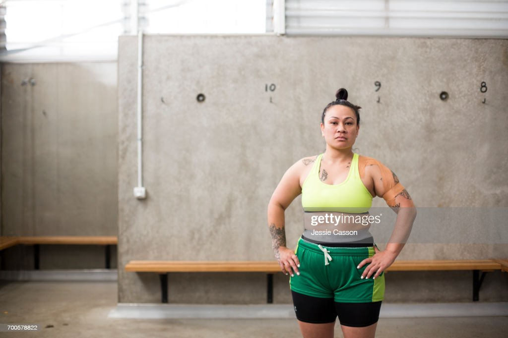 Portrait of female rugby player in sports bra and shorts standing in changing rooms looking into lens : Stock Photo