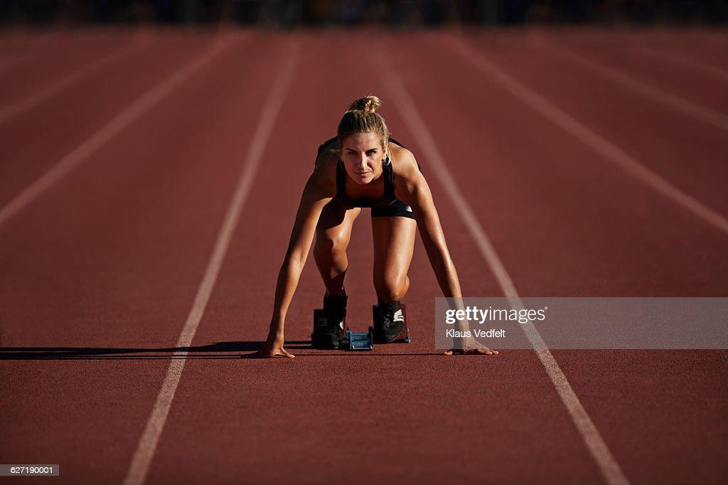 Portrait of female runner in start block : Stock Photo