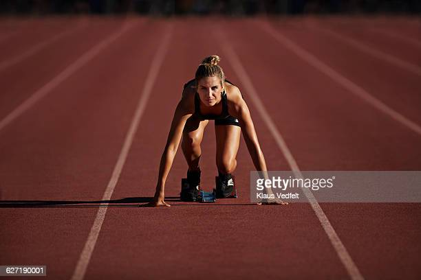 portrait of female runner in start block - atleta imagens e fotografias de stock