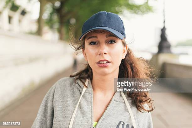 portrait of female runner wearing baseball cap - bones - fotografias e filmes do acervo