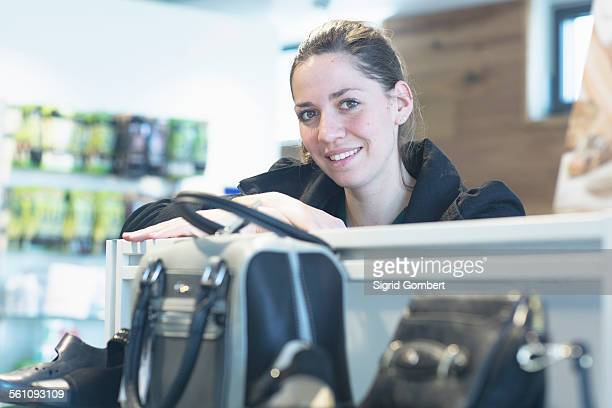 portrait of female sales assistant in shoe shop - sigrid gombert stock pictures, royalty-free photos & images