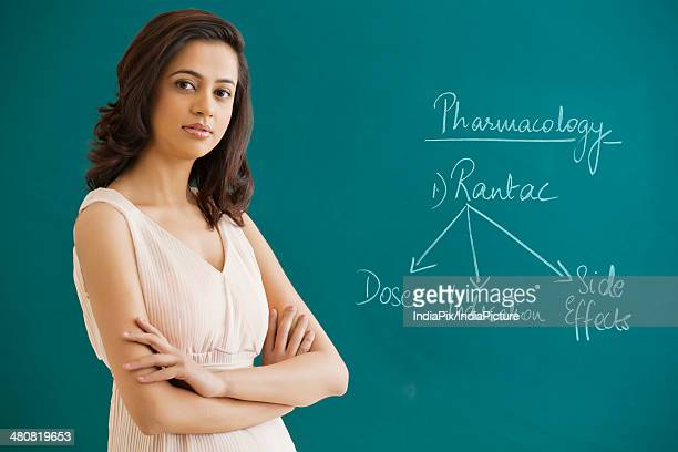 Portrait of female science professor with arms crossed standing against blackboard