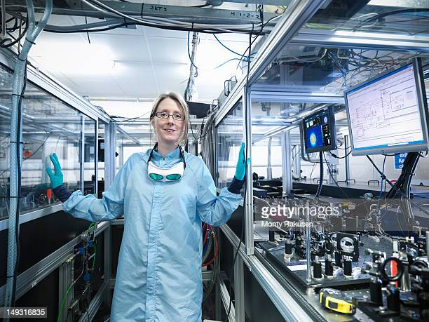 Portrait of female scientist by monitors with laser beam profiles and LabView code