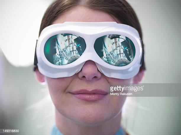 portrait of female scientist with a materials science chamber reflected in laser goggles - monty rakusen stock pictures, royalty-free photos & images