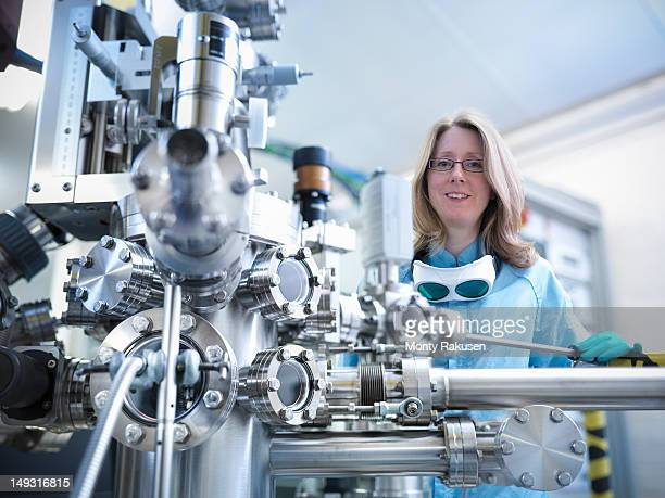 Portrait of female scientist with a materials science UHV (utltra-high vacuum) chamber