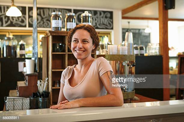portrait of female shop assistant at counter in country store cafe - heshphoto stock pictures, royalty-free photos & images