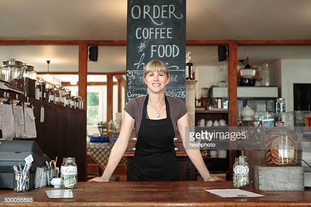 portrait of female shop assistant in country store cafe - heshphoto stock-fotos und bilder
