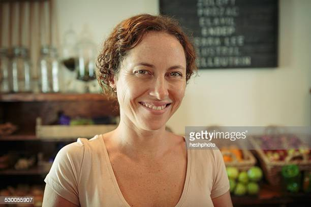 portrait of female shop assistant in country store - heshphoto stock pictures, royalty-free photos & images
