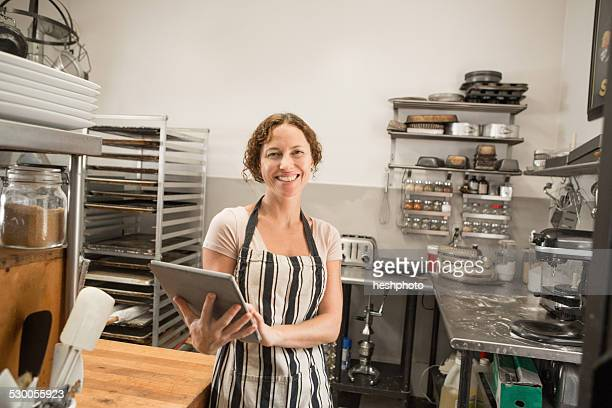 portrait of female shop assistant with digital tablet in kitchen at country store - heshphoto stock-fotos und bilder