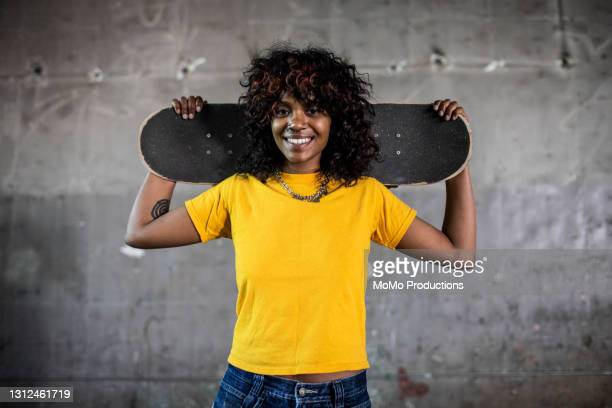 portrait of female skateboarder in warehouse environment - lifestyle stock pictures, royalty-free photos & images