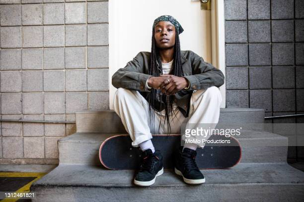 portrait of female skateboarder in warehouse environment - fashion stock pictures, royalty-free photos & images