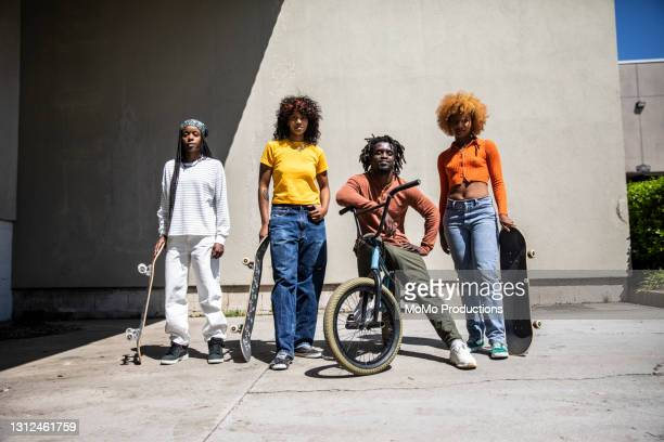 portrait of female skateboarders and bmx rider in outdoor industrial environment - black trousers stock pictures, royalty-free photos & images