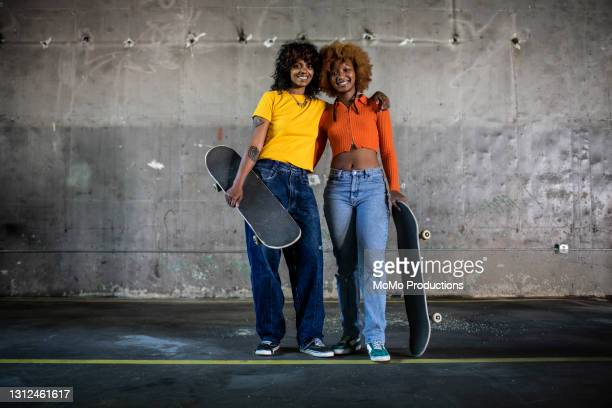portrait of female skateboarders in warehouse environment - crop top stock pictures, royalty-free photos & images