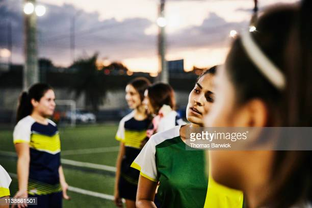 Portrait of female soccer player with teammates after game