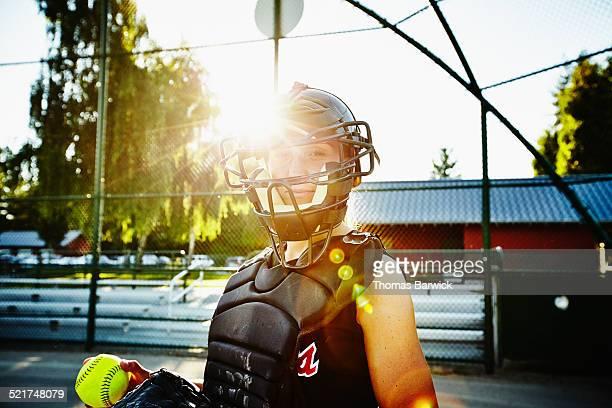 Portrait of female softball catcher holding ball