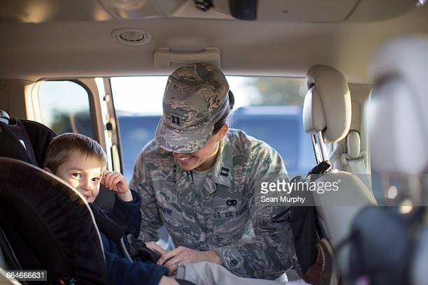 Portrait of female soldier and son in car at air force military base